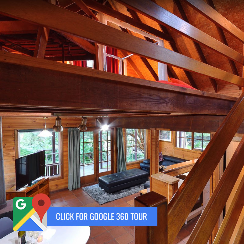 "View from stairs down to open-play living and dining room in cabin with ""Click for Google 360"" call to action"
