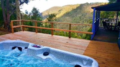 Spa on deck overlooking treetops and valley