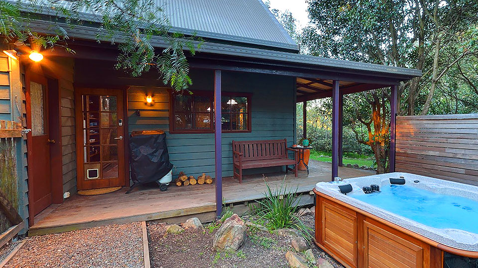 Spa in front yard looking onto cabin verandah